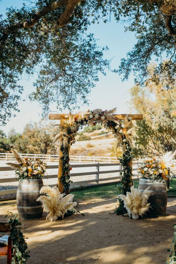 a pretty rustic fall wedding arch with greenery, white and burgundy blooms, pampas grass and matching arrangements at the base