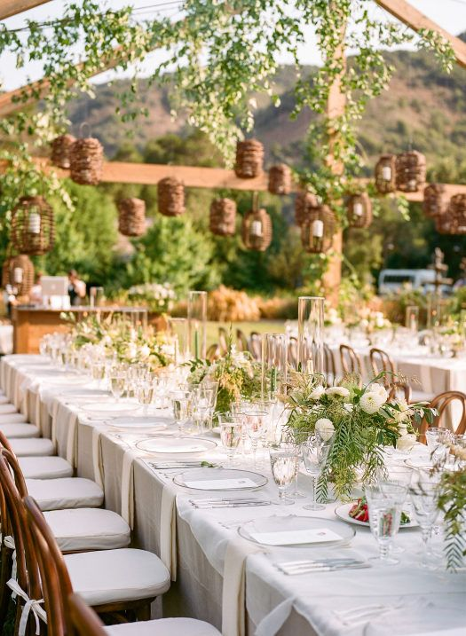a pretty secret garden wedding tablescape with neutral linens, greenery and white blooms, candle lanterns hanging over the space