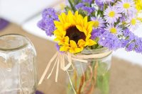 a pretty wedding centerpiece of lilac blooms and sunflowers plus mimosas is a very cool idea for a bright summer wedding