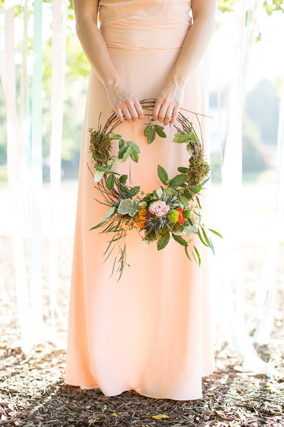 a pretty woodland hoop wedding bouquet with greenery, moss, bright blooms and thistles is a very beautiful and chic idea