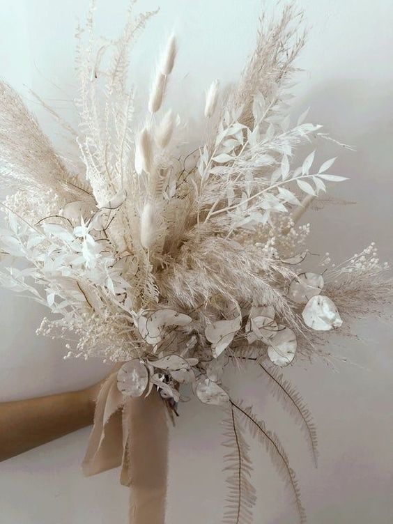 a pure white wedding bouquet of lunaria, bunny tails, pampas grass and some dried grasses and leaves plus tan ribbons is amazing