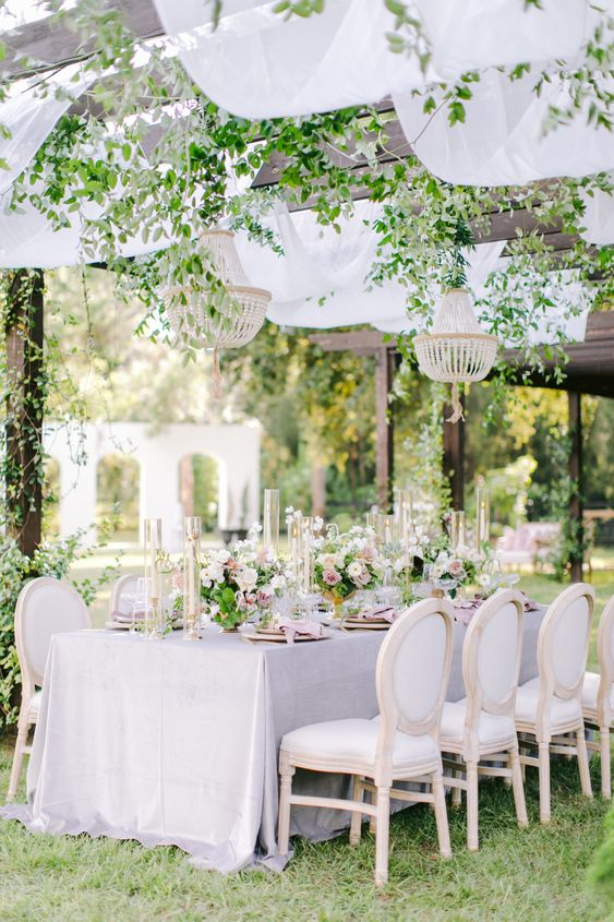 a refined garden wedding reception with lilac and pink linens, beaded chandeliers and greenery climbing, neutral and pink blooms