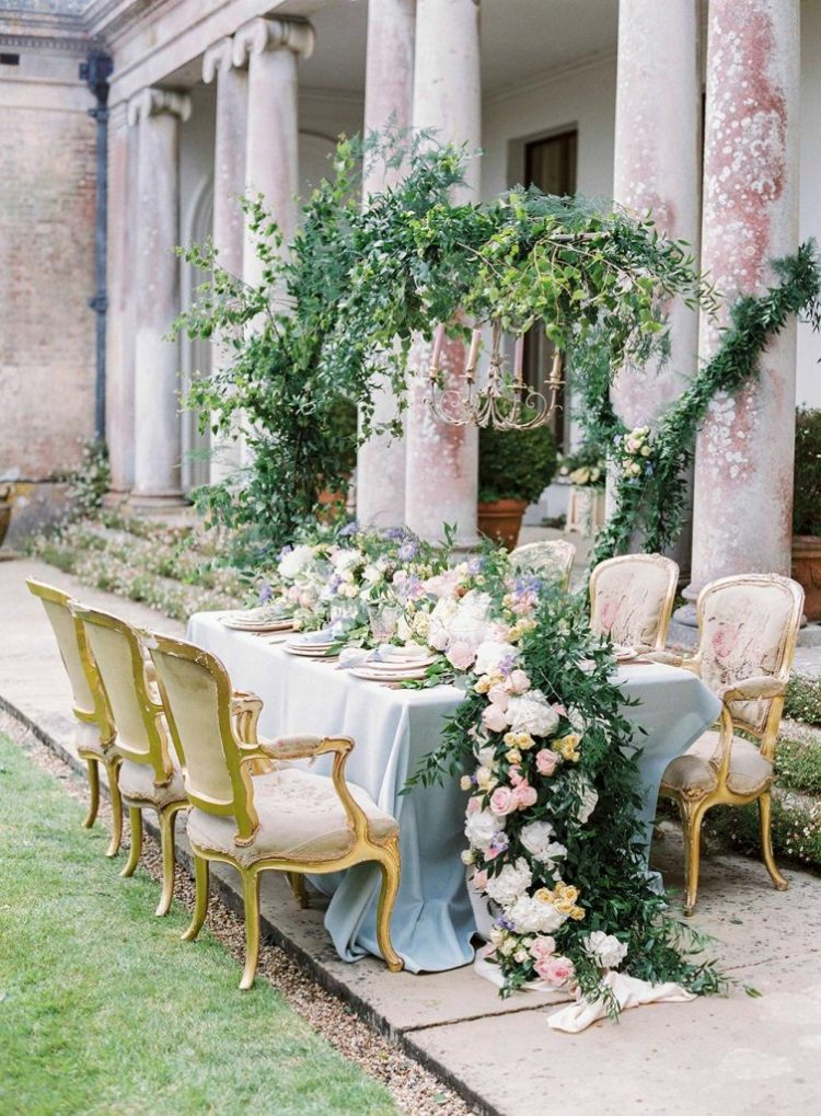 a refined garden wedding tablescape with a lush greenery and pastel bloom runner, pastel plates and linens and refined chairs