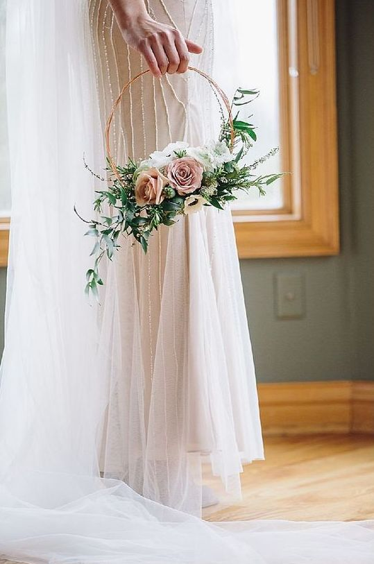 a refined hoop wedding bouquet with lush textural greenery, white blooms and pastel ones is a very delicate and chic idea
