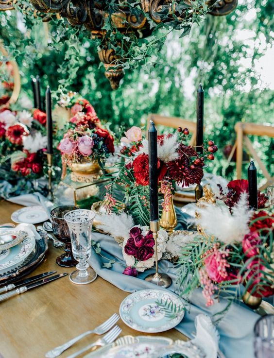 a refined secret garden wedding table setting with a blue table runner and floral plates, bold blooms and greenery, black candles and chic glasses