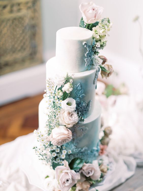 a refined wedding cake in light blue, with blush roses, daisies, blue sugar patterns and greenery is a gorgeous idea to rock