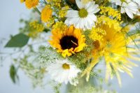 a relaxed and colorful wedding centerpiece of sunflowers, gerberas, greenery, dahlias and mimosas is a cool idea for summer or fall