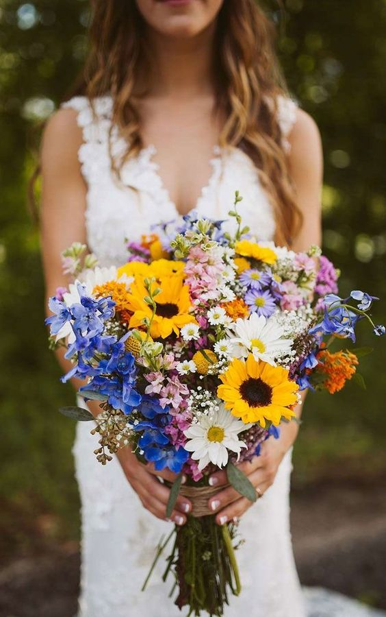a relaxed and colorful wildflower wedding bouquet with sunflowers, daisies, blue and pink blooms and baby's breath