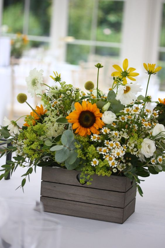a relaxed rustic wedding centerpiece in a crate, with sunflowers, daisies, greenery, billy balls, green hydrangeas and white ranunculus is wow