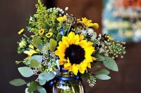 a relaxed rustic wedding centerpiece of eucalyptus, sunflowers, white and yellow blooms and candles around is a beautiful summer solution