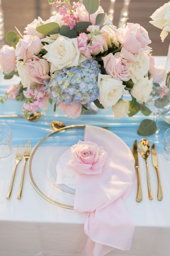 a romantic wedding tablescape with a blue table runner, pink napkins, pink and white roses, blue hydrangeas, greenery and gold cutlery