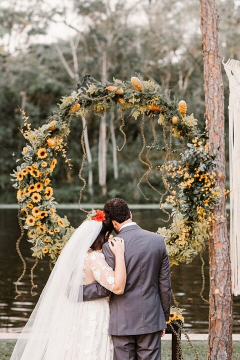 a round rustic wedding arch covered with greenery and bold yellow blooms is a pretty and colorful idea to rock