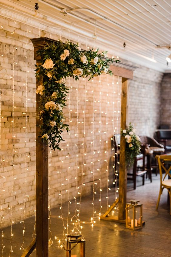 a rust fall wedding arch with greenery and peachy blooms, candle lanterns and a light curtain behind it is a very chic and cool idea