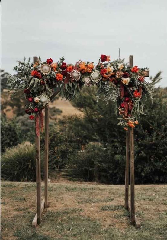 a rustic fall wedding arch decorated with greenery, orange, red, burgundy and pink blooms and much texture and dimension