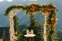 a rustic fall wedding arch of birch branches with lush greenery and super bright blooms is a bold and cool option