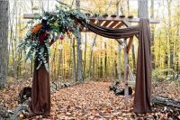 a rustic fall wedding arch with brown curtains, hanging candle bubbles, eucalyptus, some bold blooms and red apples is a very fresh and creative idea