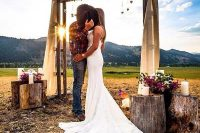 a rustic fall wedding arch with burlap, greenery and pink blooms and tree stumps around with matching blooms