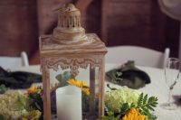 a rustic vintage wedding centerpiece with a candle lantern surrounded with green hydrangeas, sunflowers, greenery is a lovely idea