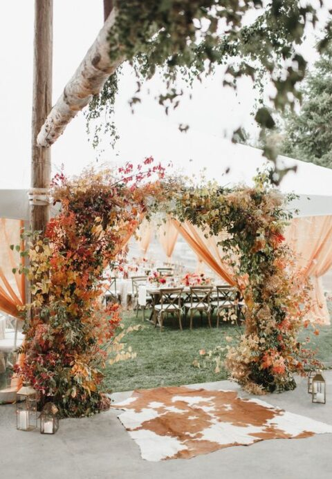 a rustic wedding arch covered with bright fall leaves and greenery plus candles around is a cool idea for fall