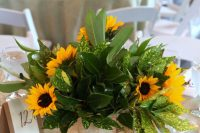 a rustic wedding centerpiece of various types of greenery and sunflowers wrapped with bark is a cool idea to rock