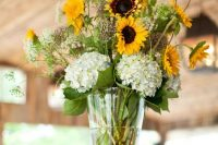 a rustic wedding centerpiece of white hydrangeas, sunflowers, wildflowers and foliage is a lovely idea for a laid-back summer wedding