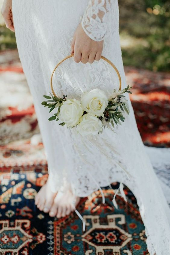 a simple and delicate hoop wedding bouquet with greenery and white roses is a lovely idea for a spring or summer wedding