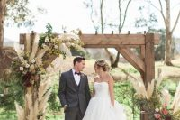 a simple and elegant rustic fall wedding arch with pampas grass, greenery, pink, blush and burgundy blooms and a printed rug is a chic idea