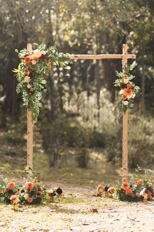a simple and stylish rustic wedding arch of branches, greenery, white, rust and burgundy blooms and deep purple touches