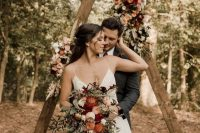 a simple boho fall triangle wedding arch with greenery, blush, peachy, rust and burgundy blooms is a lovely idea for a bold fall wedding