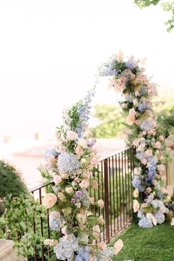 a simple floral wedding arch of blush, pink and blue blooms is a very pretty and delicate idea suitable for a garden wedding