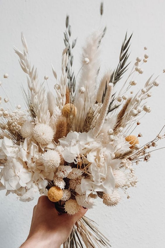 a small and cute dried flower wedding bouquet with allium, astilbe, baby's breath, wheat, some blooms and billy balls for a summer boho bride