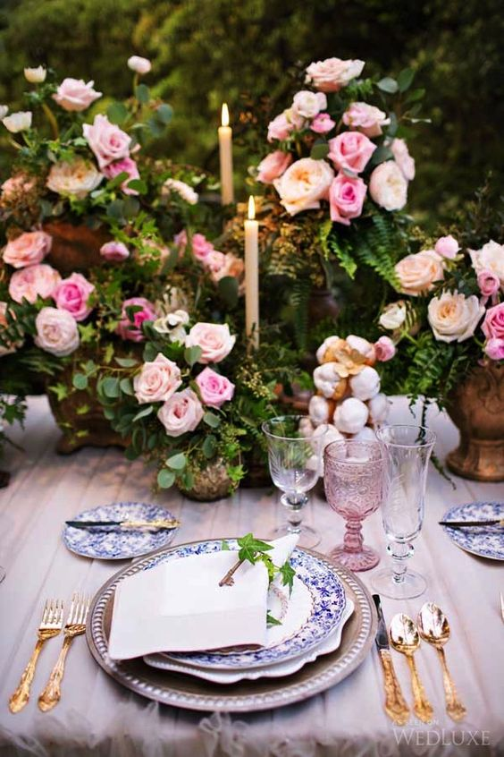a sophisticated secret garden wedding table setting with greenery and pink rose centerpieces, printed plates, blush glasses and a tablecloth