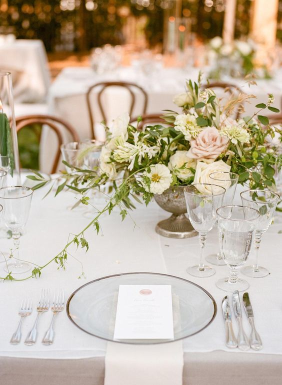a sophisticated secret garden wedding tablescape with neutral linens, sheer plates, silver cutlery and a cool neutral and pink floral centerpiece