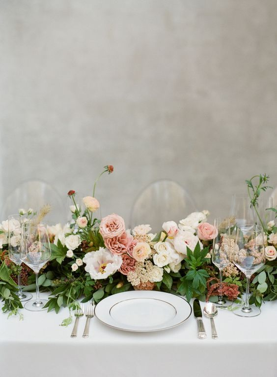 a stylish and chic garden wedding tablescape with a greenery and pink bloom runner, neutral linens and silver cutlery is wow