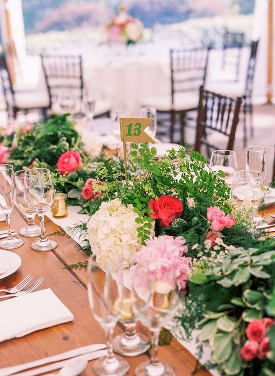 a stylish secret garden wedding tablescape with a greenery and pink bloom runner, gold candleholders, glasses and a white table runner