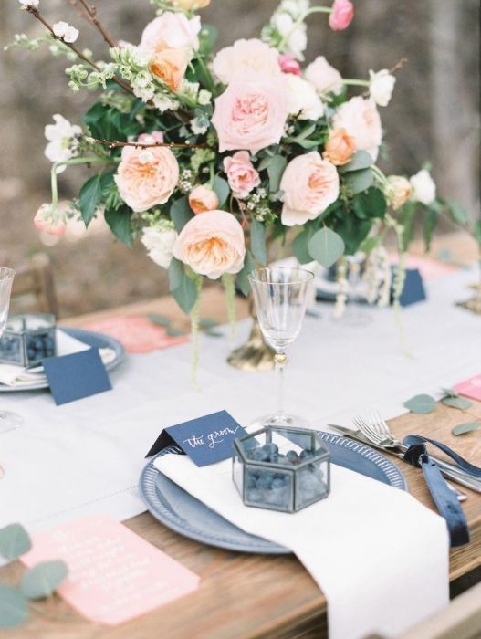 a stylish wedding tablescape with a blush wedding centerpiece, blue chargers and cards, pink menus and a neutral table runner