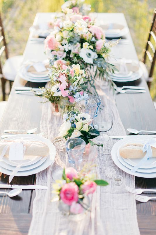 a subtle spring wedding tablescape with a neutral runner, pink, blue and white blooms, blue glasses is a great idea