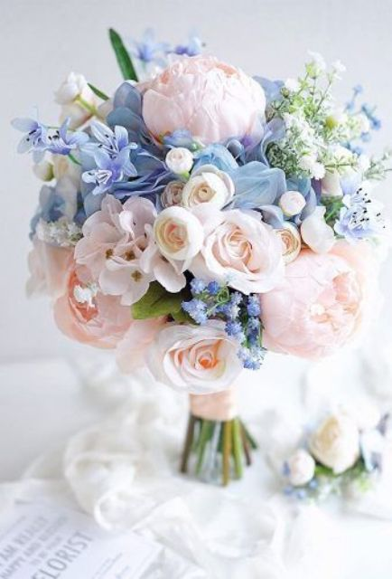 a subtle wedding bouquet of blush and blue flowers plus pink ribbons is a very beautiful and stylish idea