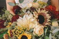 a sumptuous fall wedding bouquet of burgundy and neutral dahlias, peony roses, sunflowers, greenery and dark foliage