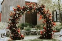 a super bold round fall wedding arch with bold blooms and white ones plus bold leaves and lots of foliage is a cool idea