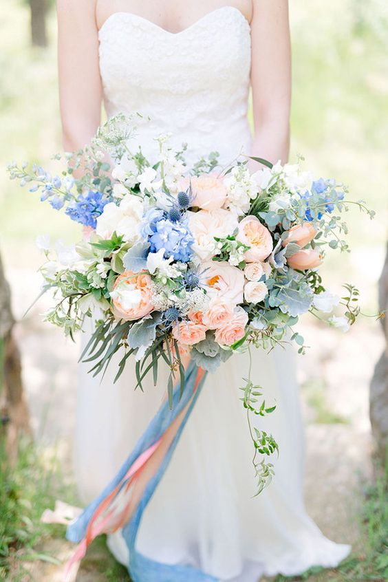 a super lush wedding bouquet of white, blush and blue blooms, with greenery, thistles and blue and pink ribbons