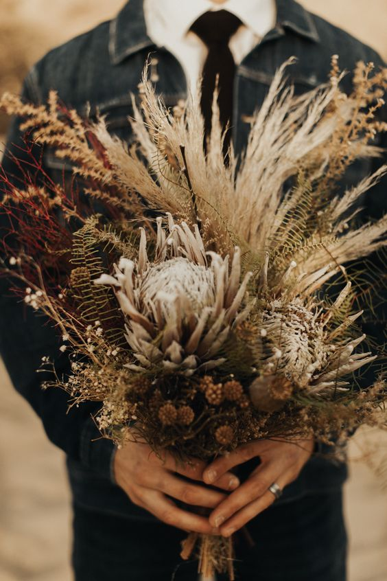 a textural and dimensional dried wedding bouquet with proteas, dried fern, pampas grass, spray painted burgundy twigs and other blooms