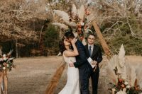 a triangle boho chic fall wedding arch with dried fronds, pampas grass, blush, orange and rust-colored blooms and boho rugs