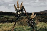 a triangle boho fall wedding arch with greenery, white and blush blooms, pampas grass and a boho rug is cool