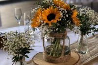 a triple rustic wedding centerpiece of vases with baby's breath and sunflowers is a gorgeous idea for a bright summer wedding in rustic style