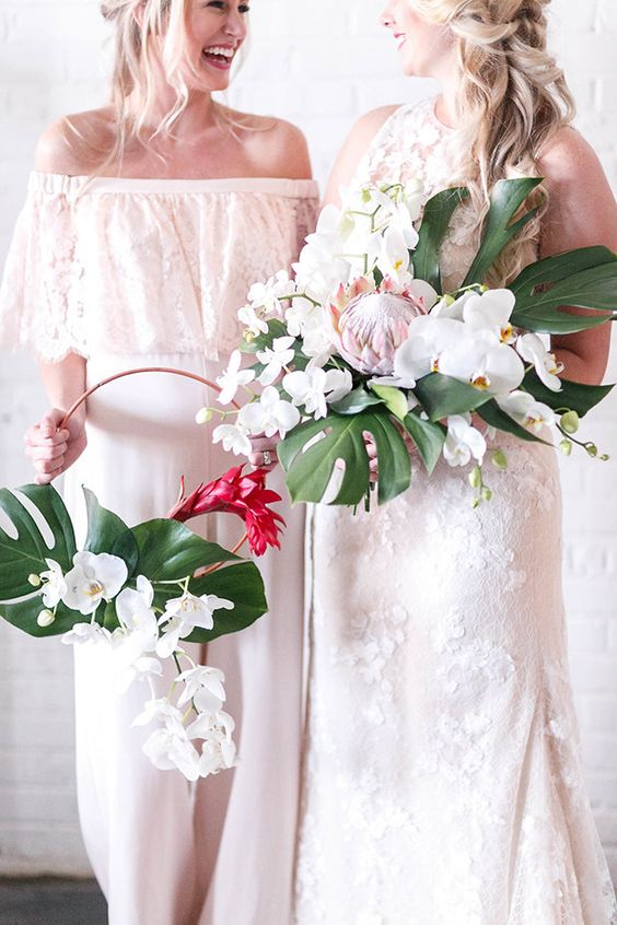 a tropical hoop wedding bouquet of white orchids, a red bloom and a couple of tropical leaves is a stylish and bold solution