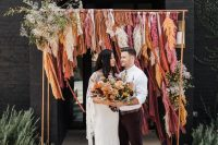 a very creative boho fall wedding arch done with long burgundy, orange, rust and pink ribbons, some white and yellow blooms and greenery