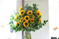 a very easy and gorgeous rustic wedding centerpiece of sunflowers and greenery is a fantastic idea for a rustic wedding