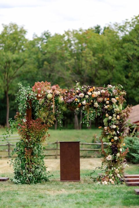 a very lush rustic fall wedding arch decorated with greenery and dried foliage, with blush, rust, deep purple, white blooms and pampas grass