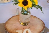 a very simple and cool wedding centerpiece of greenery, sunflowers placed on a wood slice, with a table number and burlap